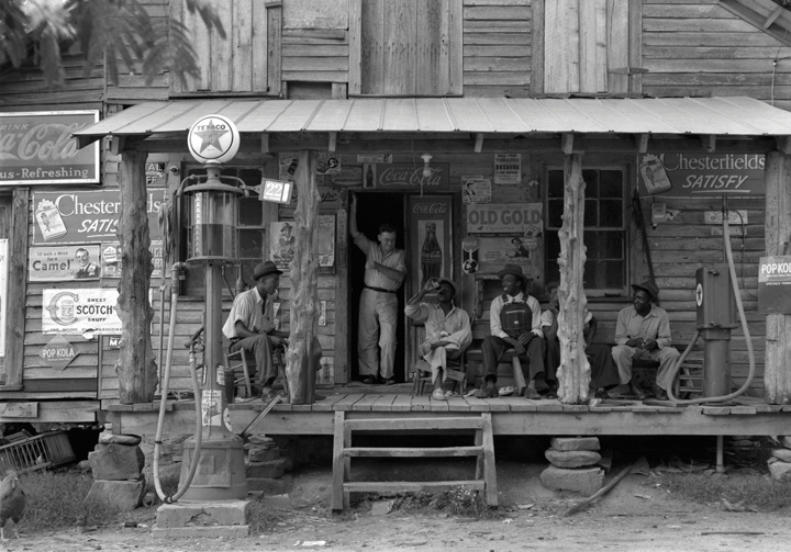 Black-and-white photo of a country store on a dirt road (Gordonton, North Carolina, 1939), showing four African American men sitting in chairs on the porch and a white man (brother of the store owner) standing in the doorway.