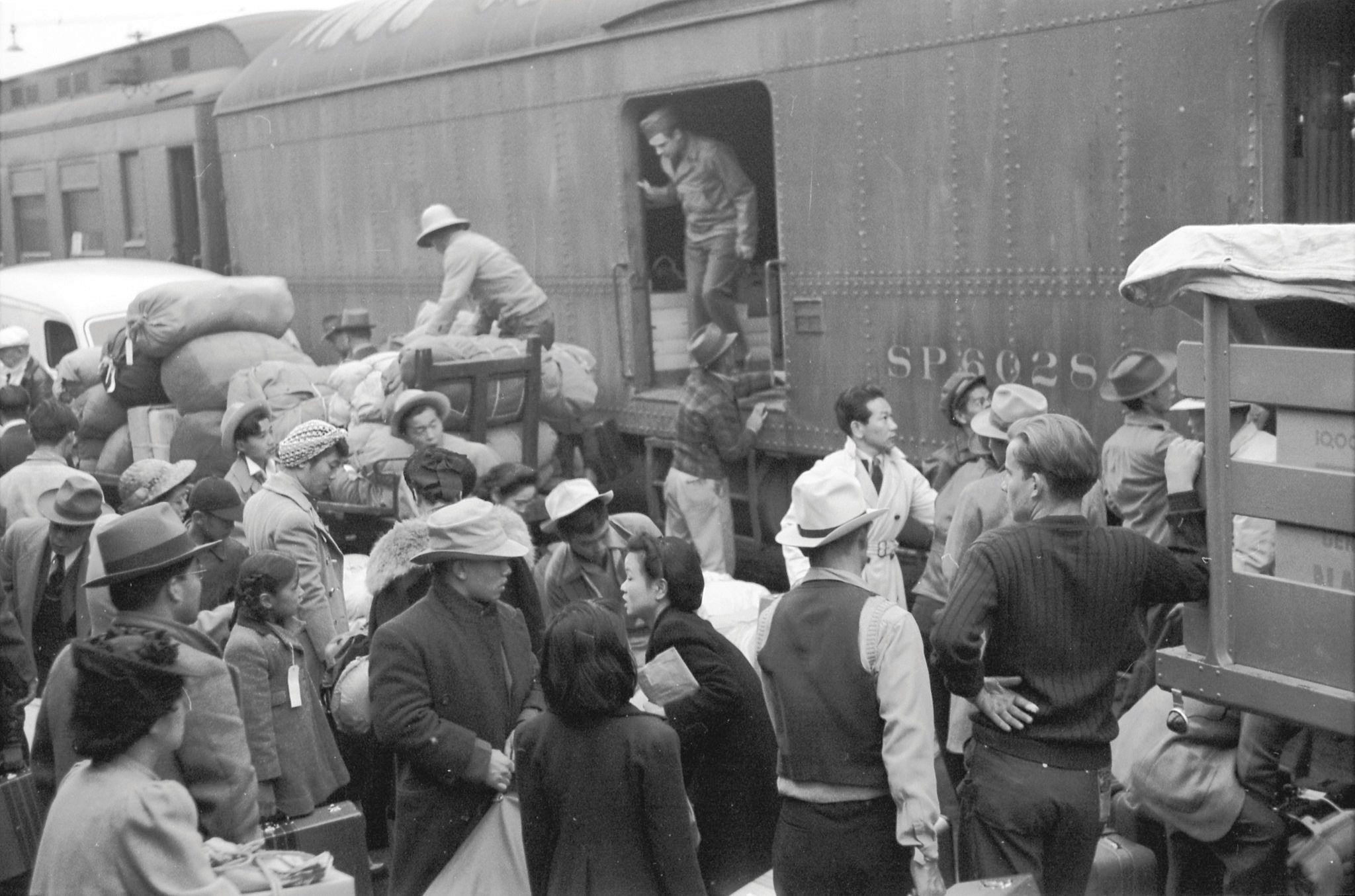 Black-and-white photo. Japanese Americans going to Manzanar gather around a baggage car at the old Santa Fe Station.