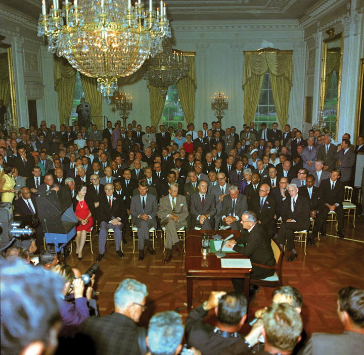 "Photo of President Lyndon B. Johnson signing the Civil Rights Act in the East Room of the White House. People watching include Attorney General Robert Kennedy, Senator Hubert Humphrey, First Lady ""Lady Bird"" Johnson, Rev. Martin Luther King, Jr., F.B.I. Director J. Edgar Hoover, Speaker of the House John McCormack. Television cameras are broadcasting the ceremony."