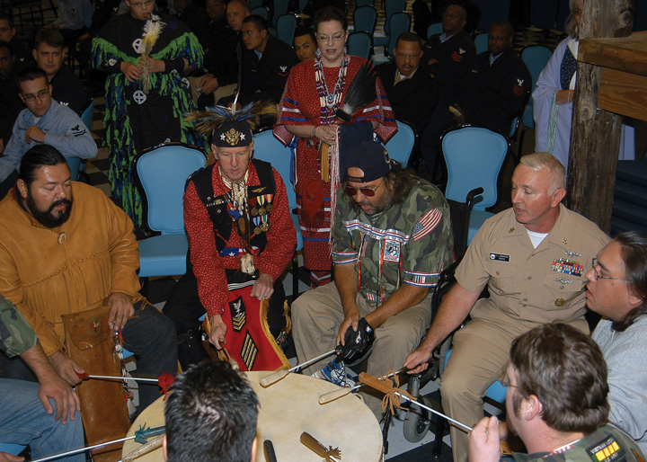 USS John F. Kennedy (CV 67) Command Master Chief, Carl L. Dassance pounds on a ceremonial drum during the Native American and Alaskan Heritage celebration Dassance, who belongs to the Ojibwa tribe, is also a member of the Native American organization Family Drum, who acknowledged their heritage by playing their ceremonial drum weekly to honor Native Americans who serve in the armed forces.