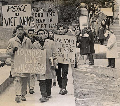 "Black-and-white photo of students protesting the Vietnam War. Many are carrying signs and placards, with messages like ""Peace in Vietnam"" and ""No more war in Vietnam."""
