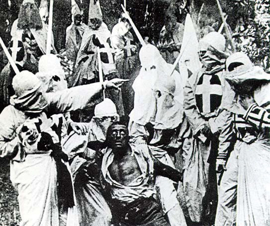 A scene from the movie Birth of a Nation (1915). Hooded Klansmen catch Gus, a black man portrayed in blackface by actor Walter Long.