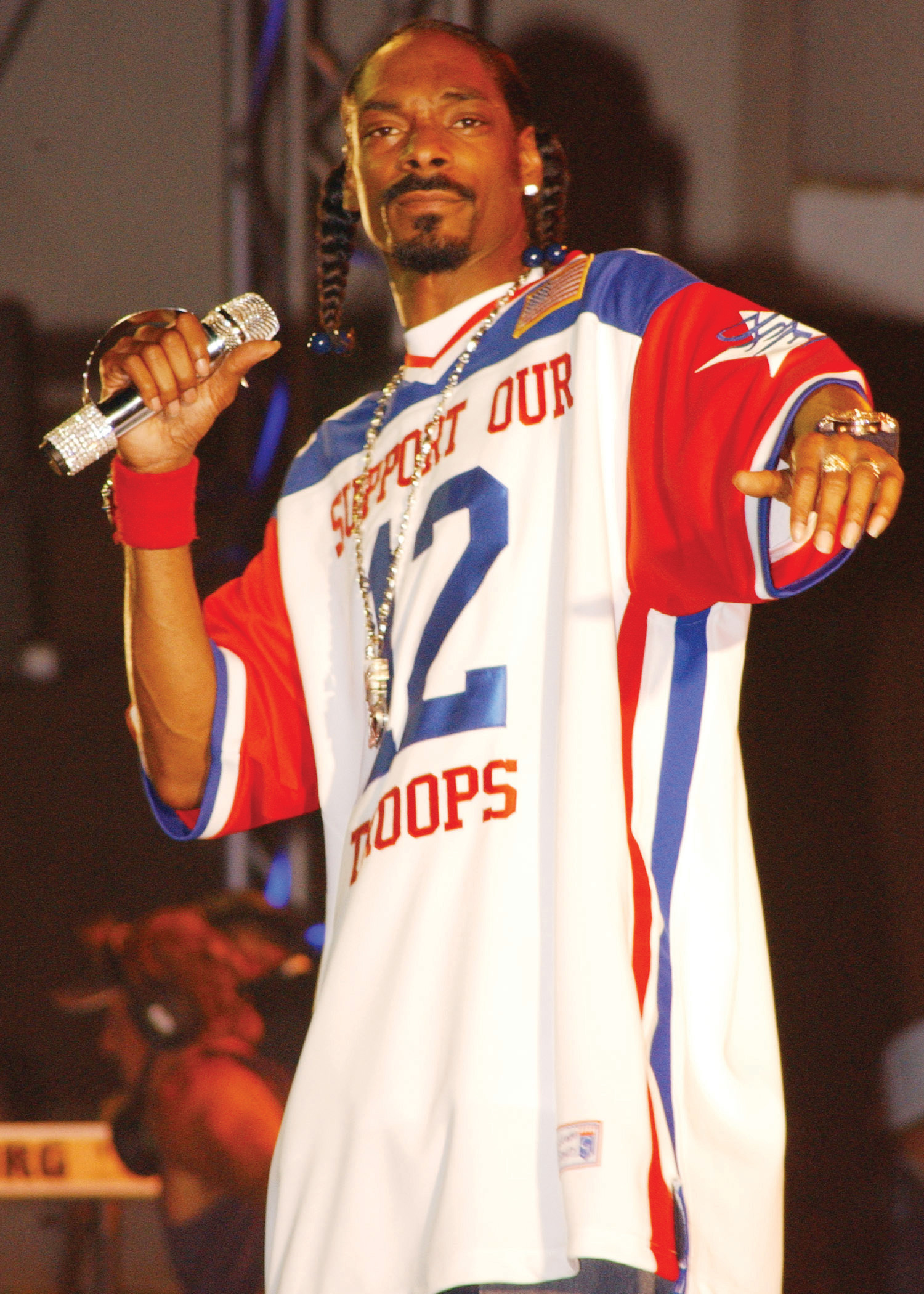 "Photo of Snoop Dogg wearing a red, white, and blue basketball shirt that reads, ""Support Our Troops."""