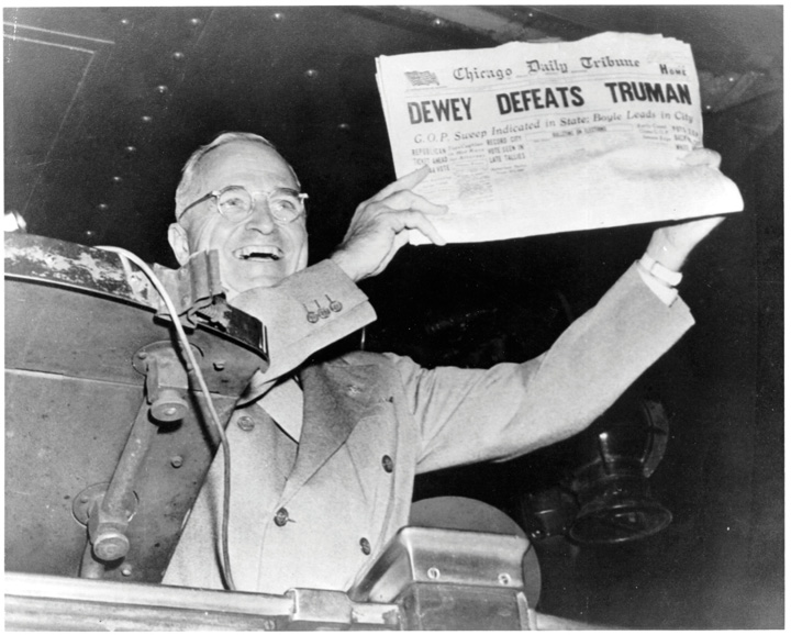 "Black-and-white photo showing a triumphant Harry Truman holding up a copy of the Chicago Daily Tribune bearing the headline ""Dewey Defeats Truman."""