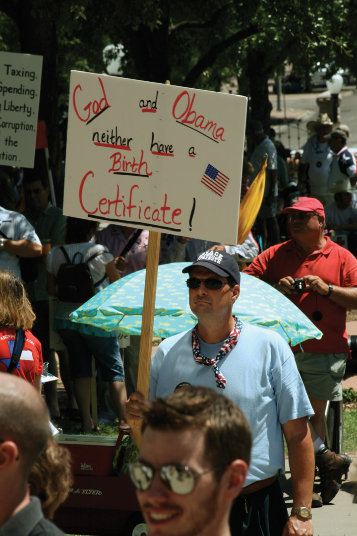"Photo of Tea Party supporters at a rally. One man holds a sign that reads, ""God and Obama—neither have a birth certificate!"""