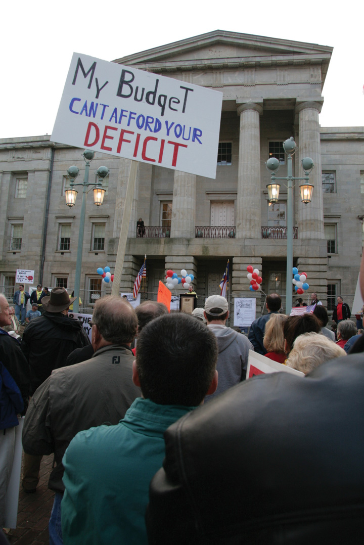 "Photo of a Tea Party rally. One sign reads, ""My budget can't afford your deficit."""