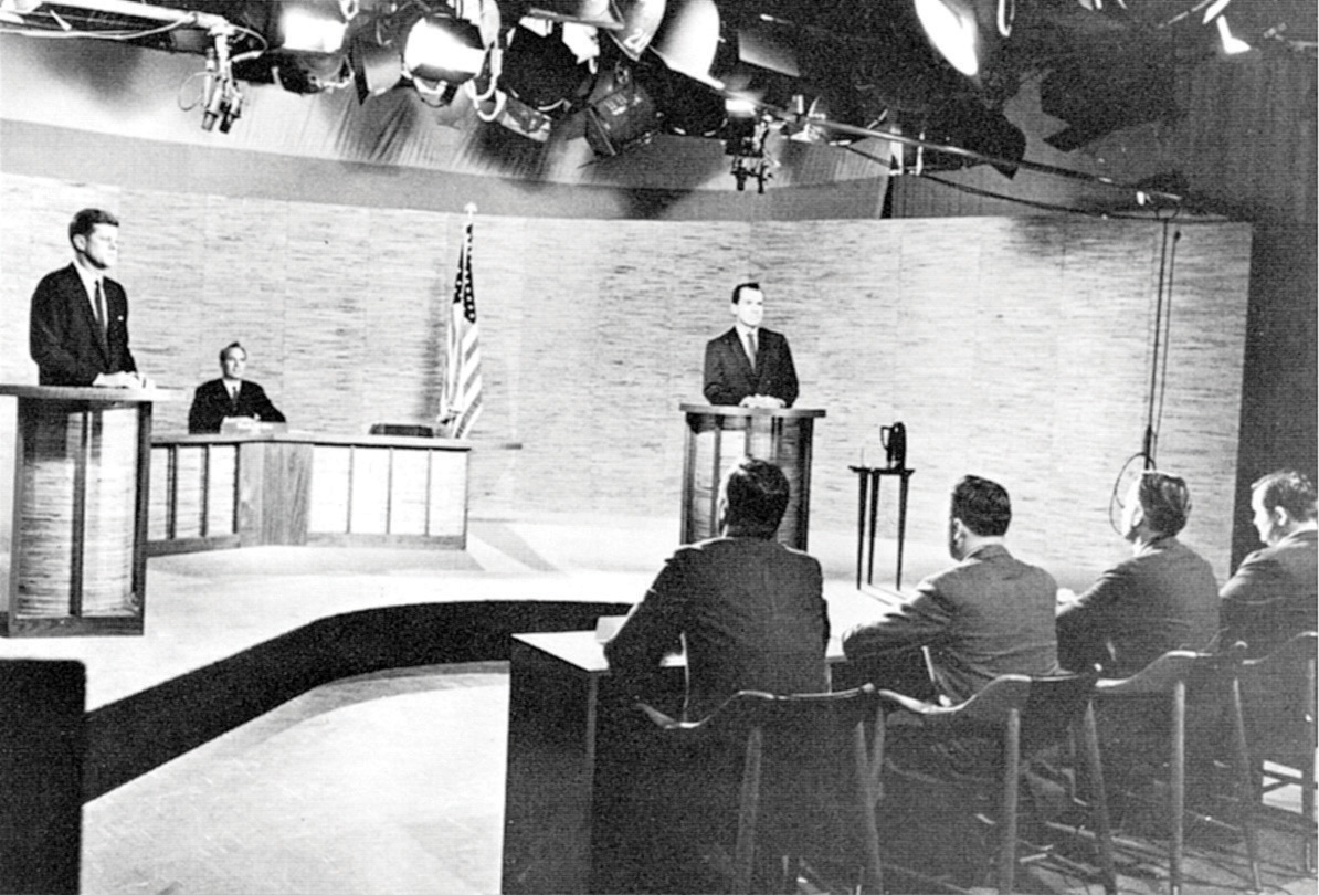 Black-and-white photo of John F. Kennedy onstage with Richard Nixon during a debate.