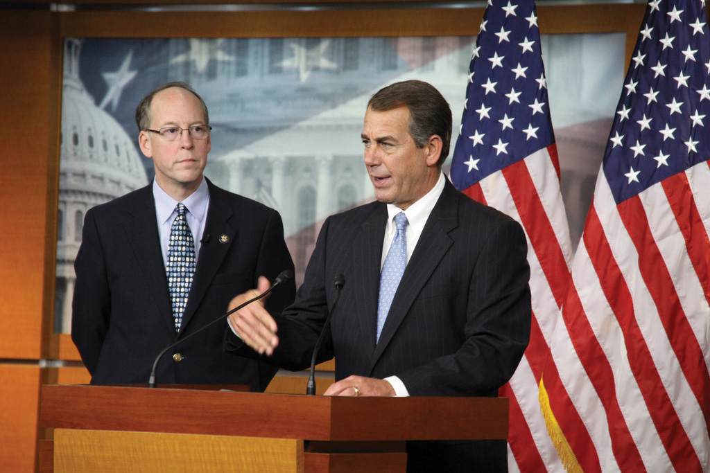 Photo of Leader Boehner (R-OH) standing next to Greg Walden (R-OR). Both are behind a podium. Two large American flags in the background.