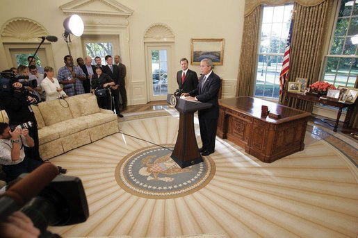 Photo of President George W. Bush in the Oval Room with John Roberts and a small crowd of journalists.