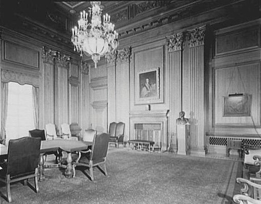 Black-and-white photo of the Supreme Court conference room. Room has a chandelier, a long table, and a fireplace.